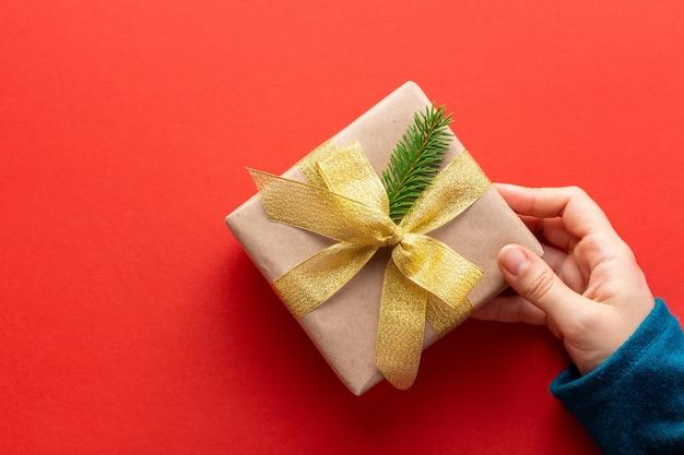 Женская рука держит подарок, оформленный в стиле минимализма на красном