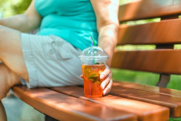 여자 손은 도시의 벤치에 앉아 aperol spritz를 보유하고 있습니다.