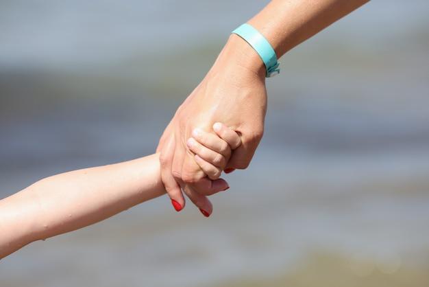 女性の手は幼児のための子供の手の親のサポートを保持します