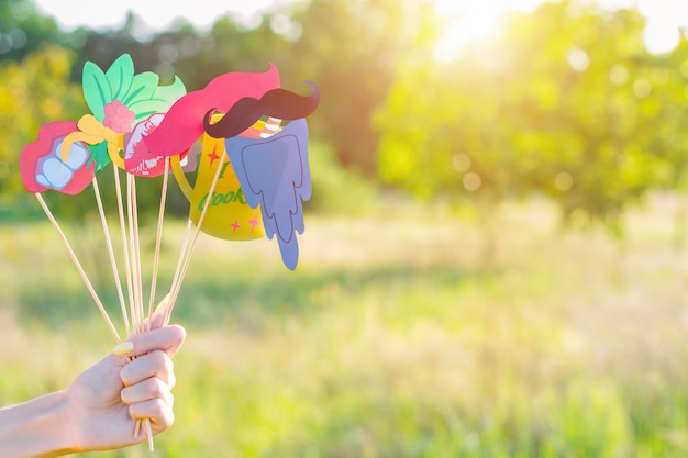Woman hand holds colorful photo props mustaches lips teeth on summer spring sunny green yellow sun light field sunset. photoshoot photo session party festival carnival celebration requisite concept.