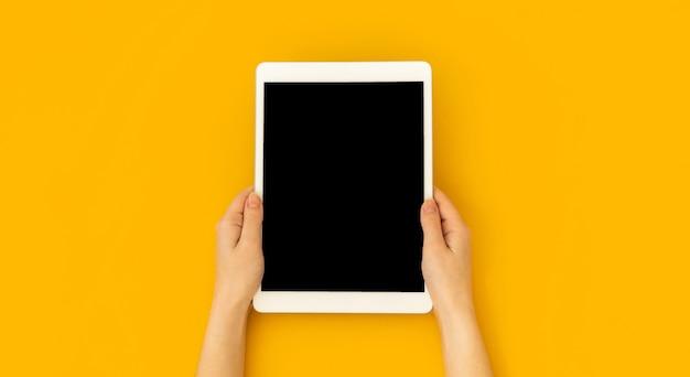 女性の手は、空白の画面、教育とアプリケーションのコンセプトテンプレート、明るい黄色の背景、上面図とコピースペースの写真でデジタルタブレットのモックアップを保持します