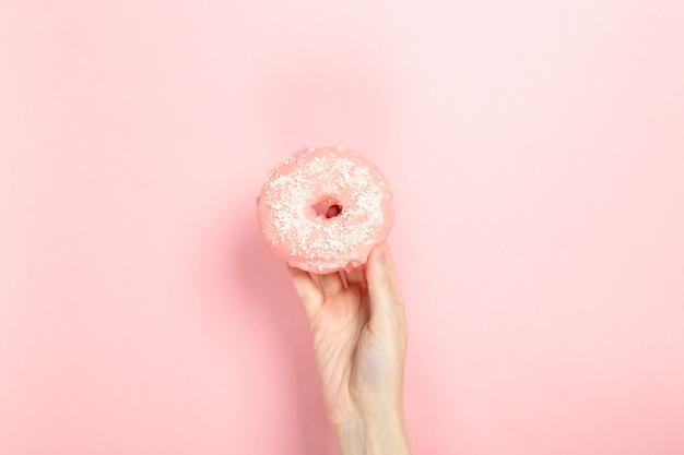 女性の手を保持するピンクのアイシングとココナッツのペストリーのトッピング、ピンクの背景