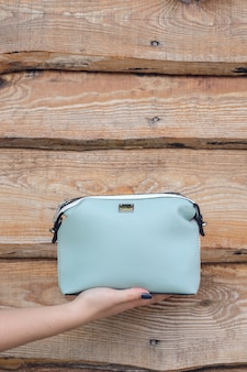 Woman hand holds handbag on wood wall