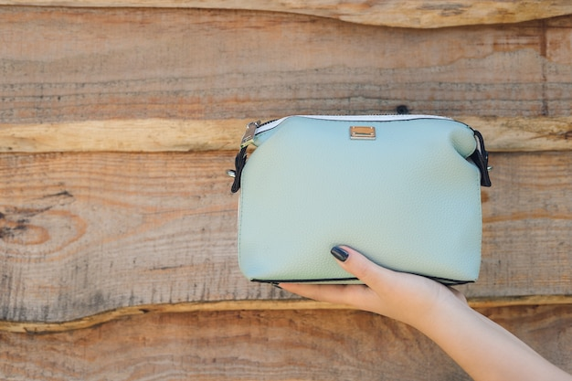 Woman hand holds handbag on wooden