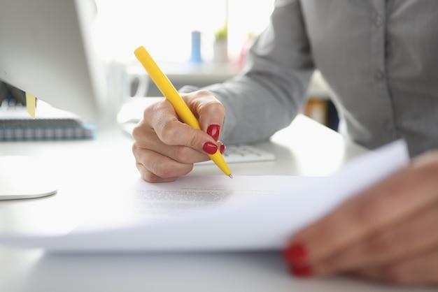 Женская рука держит ручку и подписывает документ