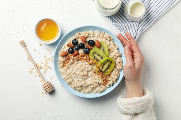 Woman hand holds plate with oatmeal porridge with fruits, top view