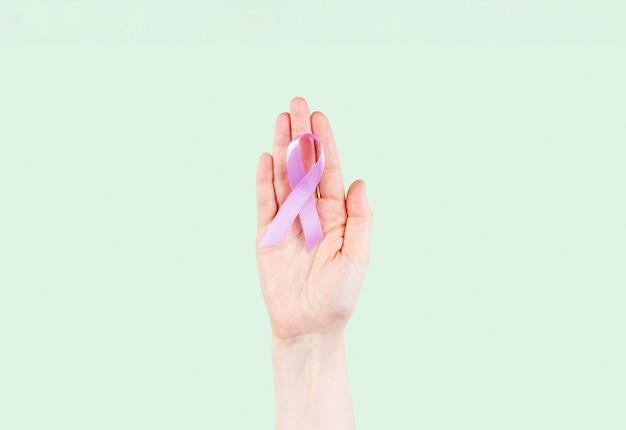여자 손 보라색 리본을 보유하고있다. 세계 암의 날. 밝은 보라색 또는 라벤더 리본은 모든 암을 나타냅니다.