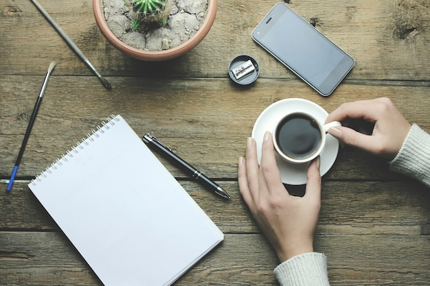Woman hand holiding cooffee and notebook and pen on table