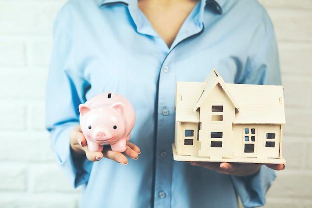 Woman hand housemodel and piggy bank