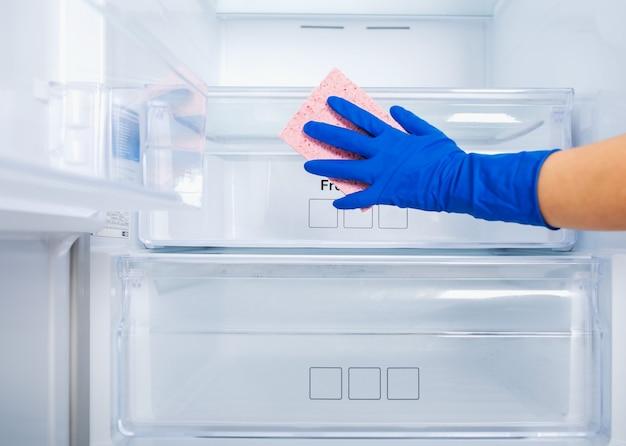 파란색 고무 보호 장갑과 분홍색 스폰지에 여자 손을 씻고 냉장고 선반을 청소합니다.
