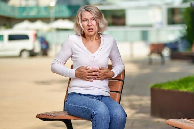 여자는 거리에서 아파 배꼽에 손을.