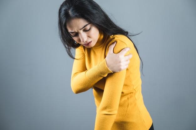 Женщина рука в руке боль на сером фоне
