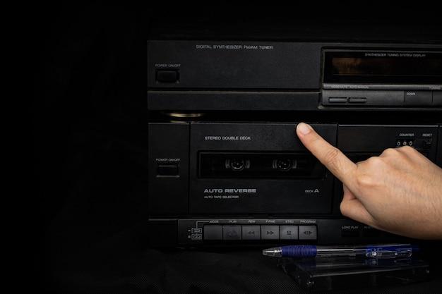 오래된 플레이어 오디오에 소형 카세트 테이프를 삽입하는 여성의 손은 복고풍 기술입니다.