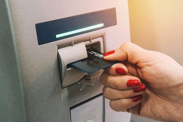 Atm에 신용 카드를 삽입하는 여자 손. 그 소녀는 atm에서 돈을 받습니다. 카드가 단말기에서 나옵니다.