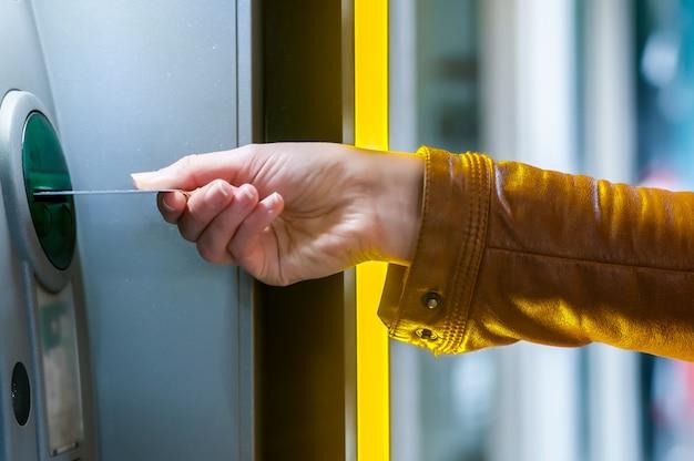 女性の手は、atmにクレジットカードを挿入