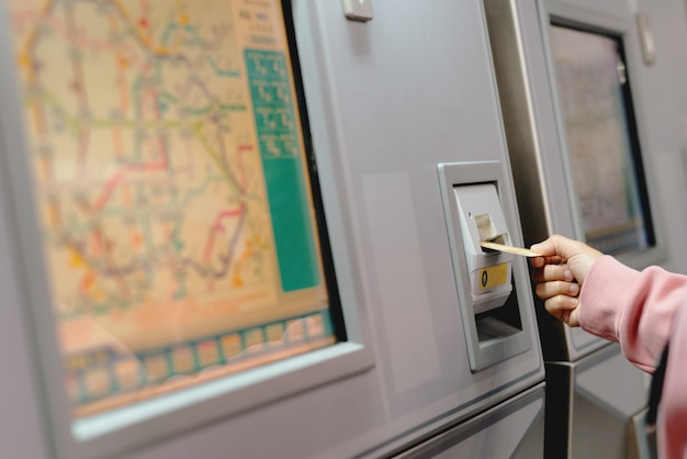 Woman hand inserts card to buy subway train ticket in machine.