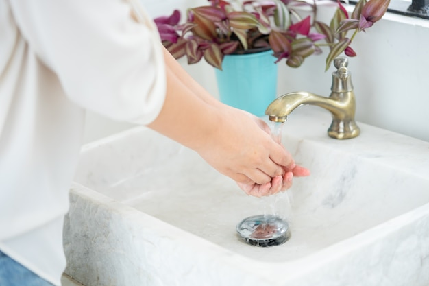 The woman hand is going to open the faucet to wash hands. to maintain cleanliness