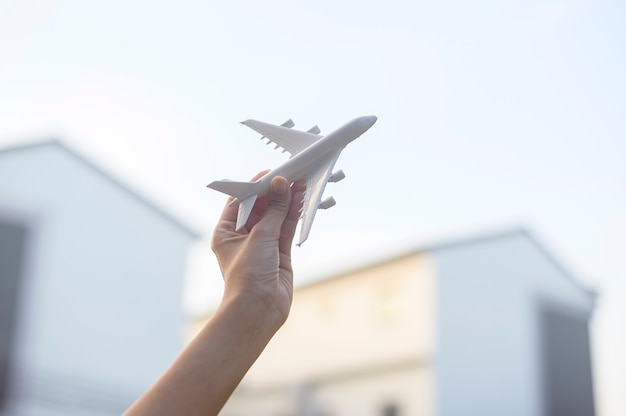 Woman hand is holding airplane model against sunset , holiday travel , business conservation transportation concept.