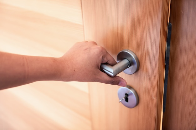 Woman hand is holding door knob while opening a door in bedroom.