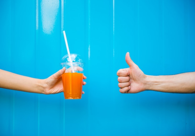 Woman hand is holding juice against the blue wall.