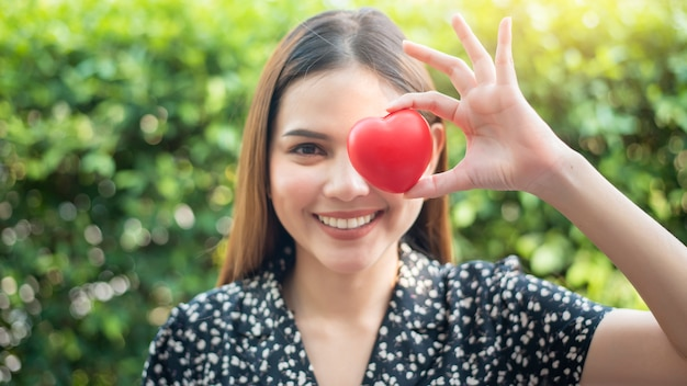 Woman hand is holding red heart