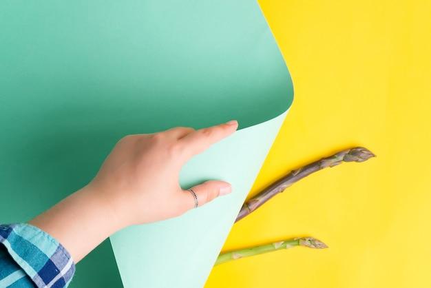 女性の手は、天然アスパラガスの新しい芽と黄色の背景にパステルターコイズ色の紙のシートを回しています。