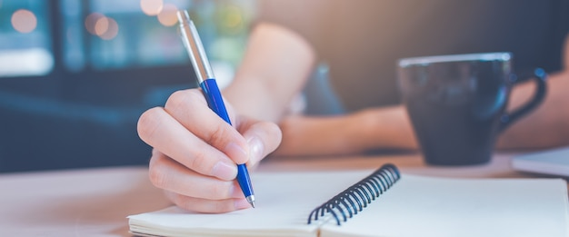 Woman hand is writing on a notepad with a pen in office.