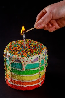 Woman hand light up a candle on colorful birthday cake.