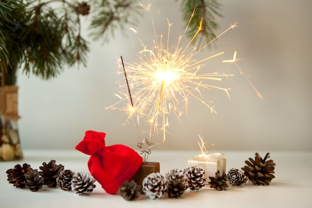 Woman hand lighting festive sparkles near pine cones, christmas tree and red christmas hat. new year party burning sparkler closeup on white background. fireworks, shining fire flame. christmas light.