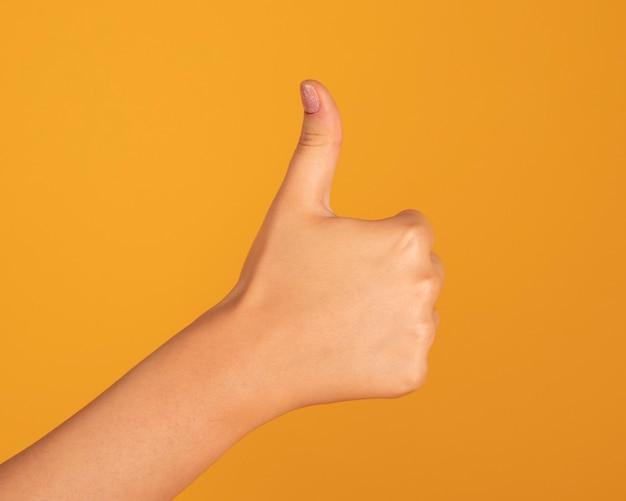 女性の手が黄色の空間でokのしぐさを作る