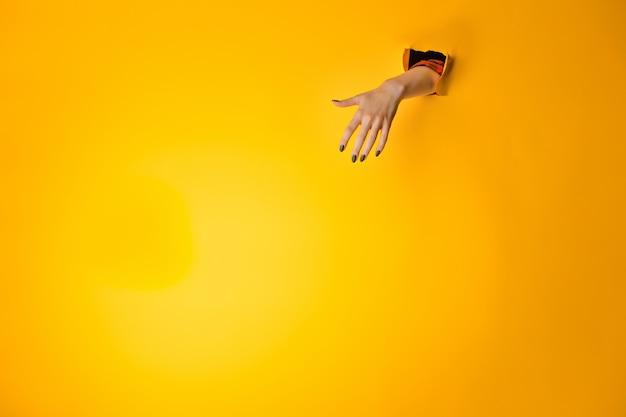 黄色の背景で隔離の紙の穴からサインを作る女性の手