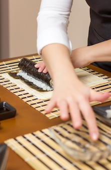 Woman hand moistening with water a sushi roll edge