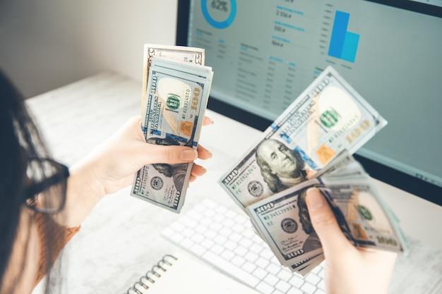 Женщина руки деньги с графиком на экране компьютера