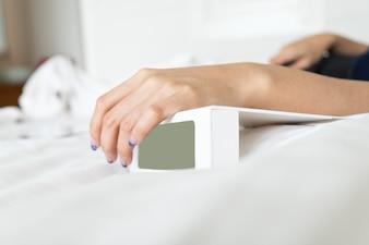 女性の寝室で白いデジタル目覚まし時計に手します。