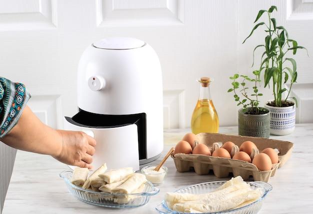 여자 손 오픈 에어프라이어 트레이입니다. 냄비에 작은 식물이 있는 주방의 나무 테이블에 흰색 튀김기 또는 오일 프리 프라이어 기기, 집게, 투명 베이킹 접시 및 계란 트레이가 있습니다(에어 프라이어)