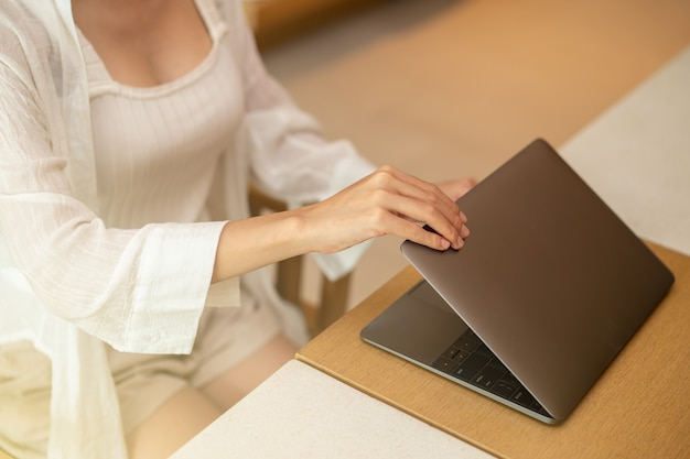 Woman hand open or close laptop on wood table.