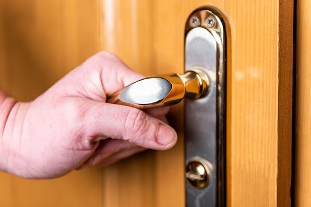 女性の手がドアを開ける