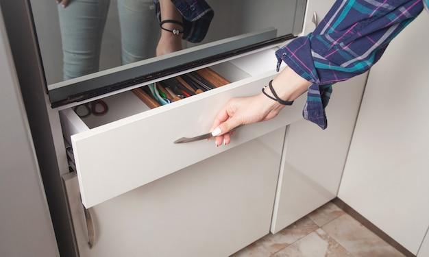 女性の手がキッチンの引き出しを開きます。