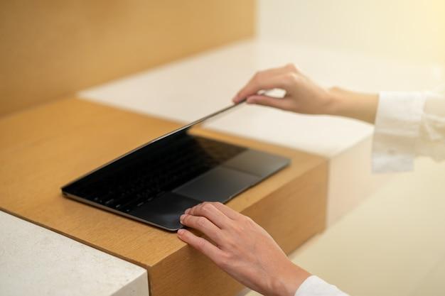 Женщина рука открыть или закрыть ноутбук на деревянный стол.