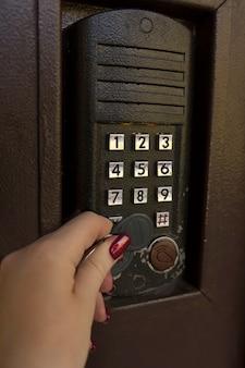 磁気キーでインターホンを開く女性の手