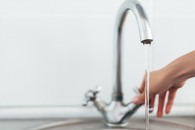 台所の金属製の洗面台が付いている銀の蛇口または水栓を開く女性の手。