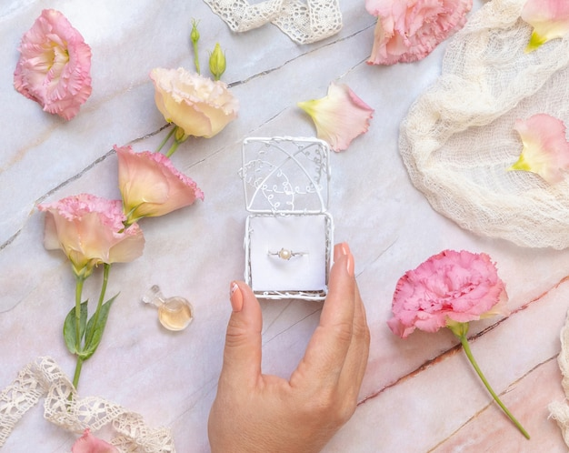 Woman hand opens a gift box with a pearl ring with light pink flowers around