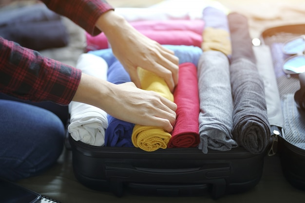 Woman hand pack clothes in suitcase bag on bed