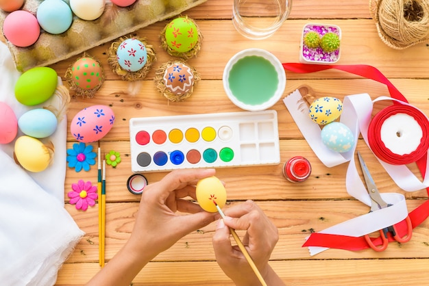 Woman hand painting easter eggs. happy family preparing for easter.