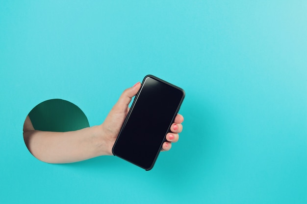 Woman hand in the paper hole holding smartphone