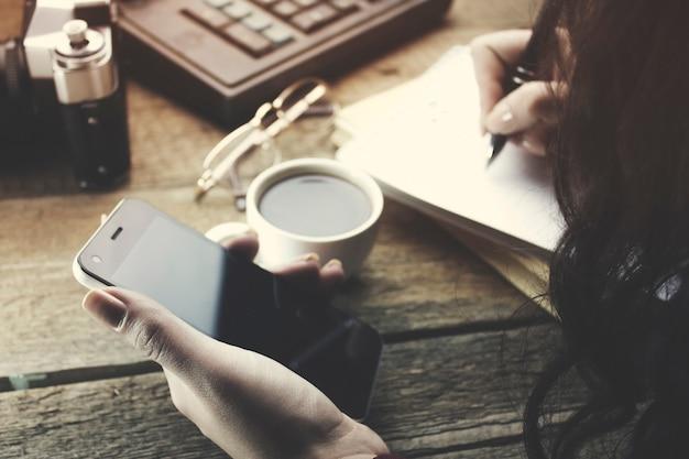 작업 테이블에 노트북에 여자 손 펜과 전화 쓰기