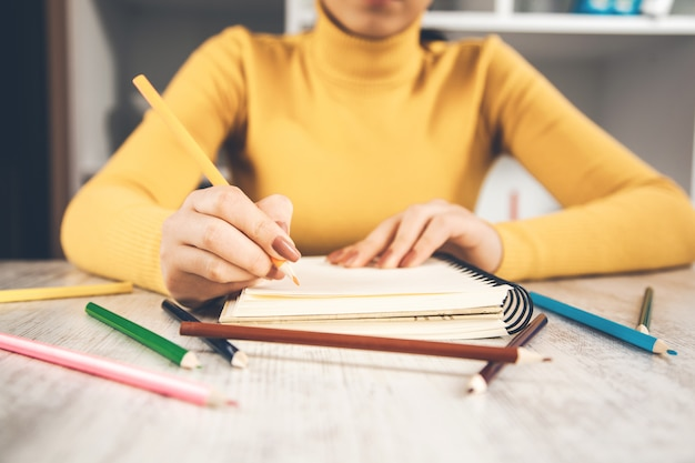 テーブルの上のメモ帳で女性手鉛筆