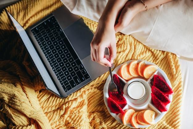 여자 손은 노트북으로 작업하는 동안 침대에서 아침 식사를 위해 과일을 데리러
