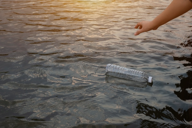 Woman hand to pick up the used waste plastic bottle on the water in a canal