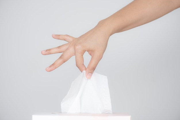 Woman hand picking white tissue paper from tissue box on gray background